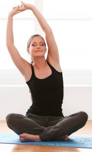 Young and beautiful woman doing yoga exercises at home